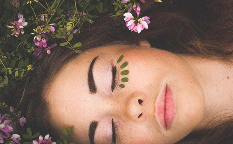 Close up of woman's face as she sleeps outdoors on a flowery field with five little leaves under her left eye.