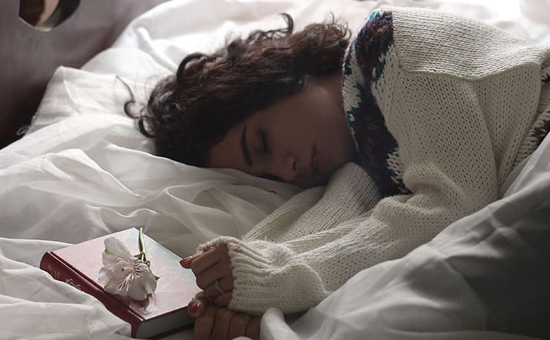 Woman in sweater sleeping on her side in her bed, with a book and a flower next to her.