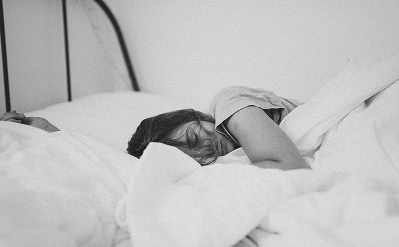 Black and white image of woman in her white sheets sleeping too much.