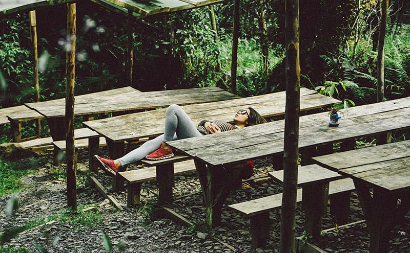 Woman in sunglasses taking a nap in the woods on a bench.