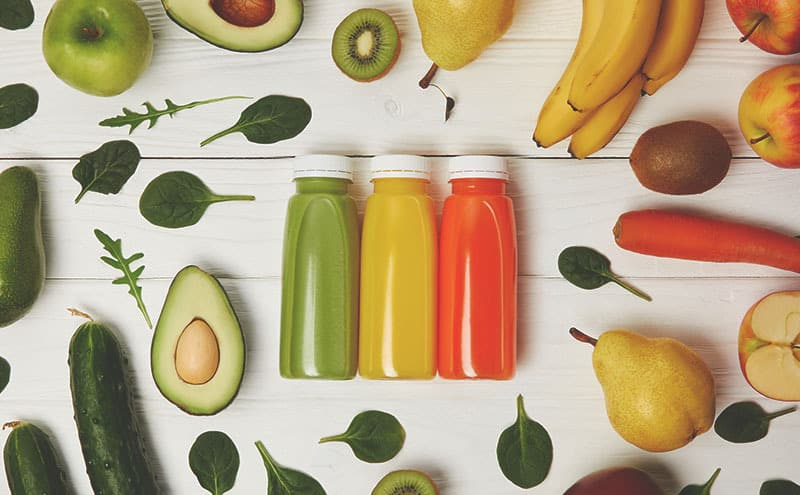 Avocados, a carrot, leaves, pears, cucumbers, kiwis, apples and bananas surrounding a green, a yellow and orange bottles, in an attempt of keeping the juices fresh.