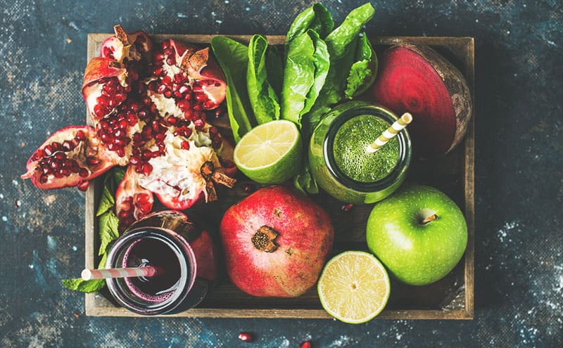 A tray with a pomegranate, apples, lime and salad leaves, with two bottles of juice with straws.
