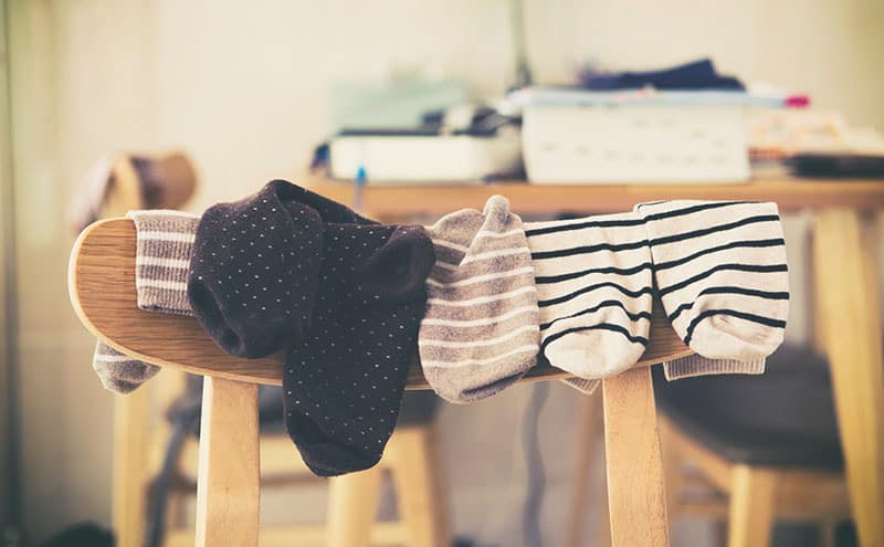 Socks used for sleeping with them are hanging from a chair.