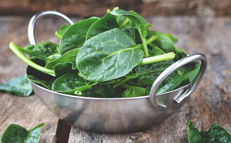 A metal bowl of spinach leaves on a wooden table.