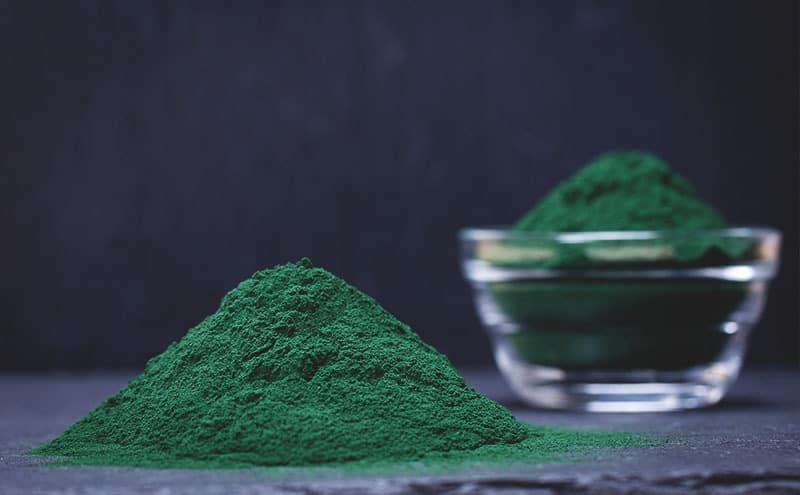 A pile of the best spirulina powder in front of a glass bowl of it.