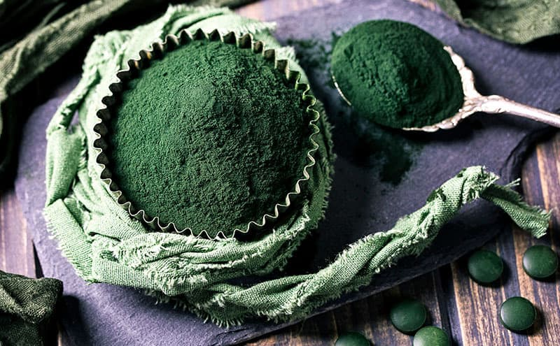 A muffin paper full of spirulina in powder form, next to a spoon of spirulina, surreounded by spirulina pills.