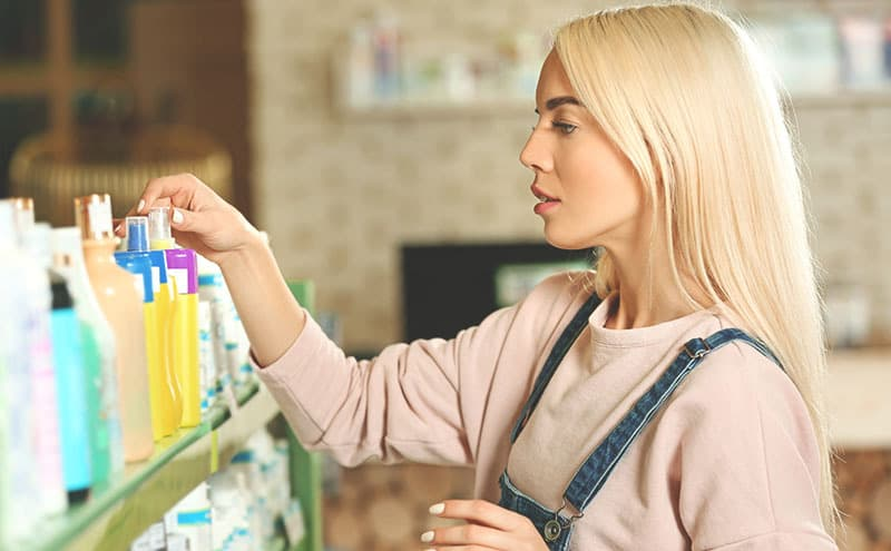 Attractive blond woman browsing through a shelf, looking for the best sulfate free dandruff shampoo in the store.