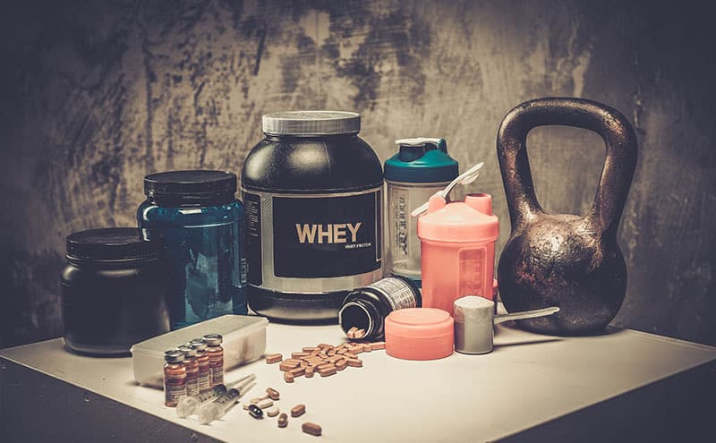 Different kinds of pre-workout supplements gathered on a table, in an attempt to find the strongest one.