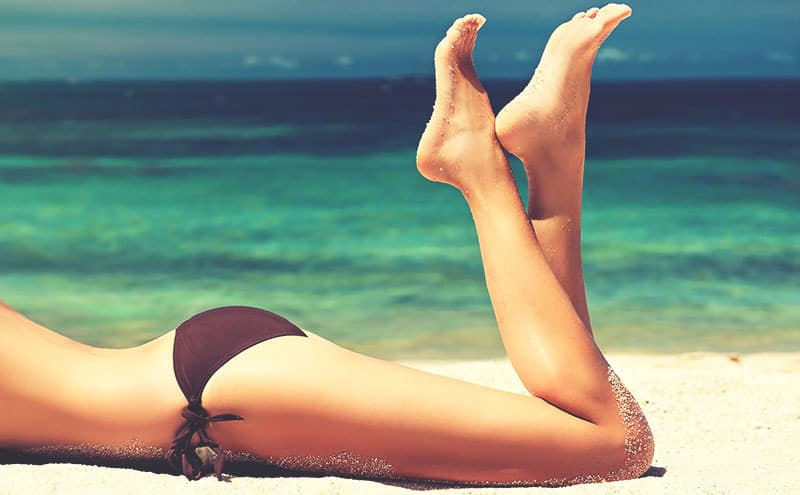 Woman at the beach, in bikini, enjoying the aftermath of one of the best waxing kits for hair removal.