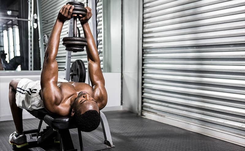 Man at gym exercising on weight bench with a dumbbell.