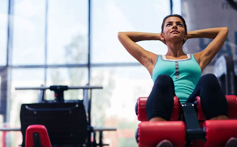 Woman doing sit-ups at gym on a weight bench.