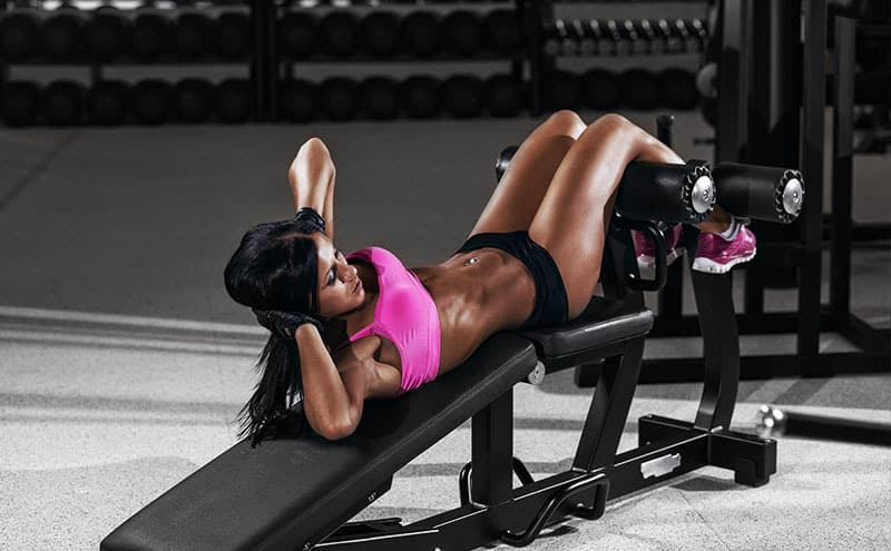 Woman working out at the gym on one of the best adjustable weight bench.