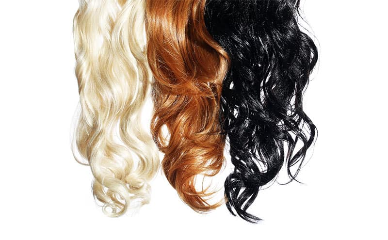 Blond, brown and black clips of hair placed next to each other on white background.