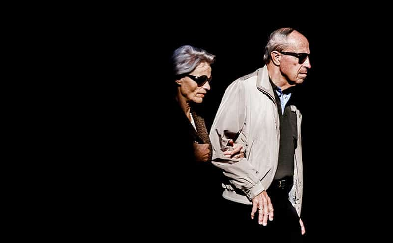 Mature couple with grey hair wearing sunglasses, walking outdoors.