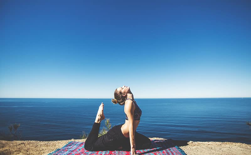 Woman doing yoga at the sea side.