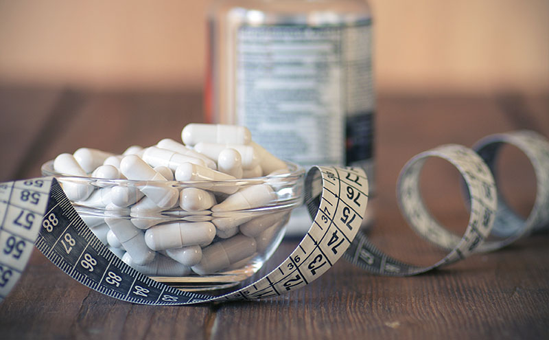 Tape measure with white capsules in a glass bowl in front of a supplement box, on dark wooden table