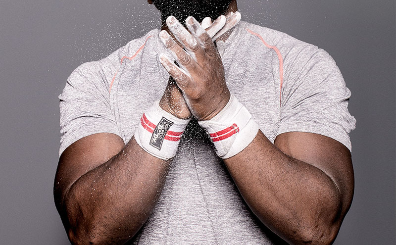 Strong, muscly african american man rubs hands with white powder.