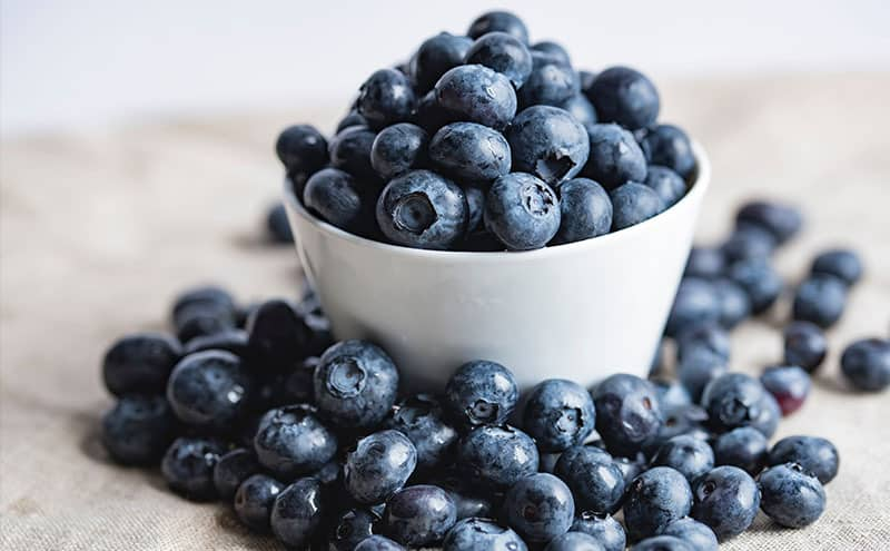 A white bowl full of blueberries, surrounded by blueberries.