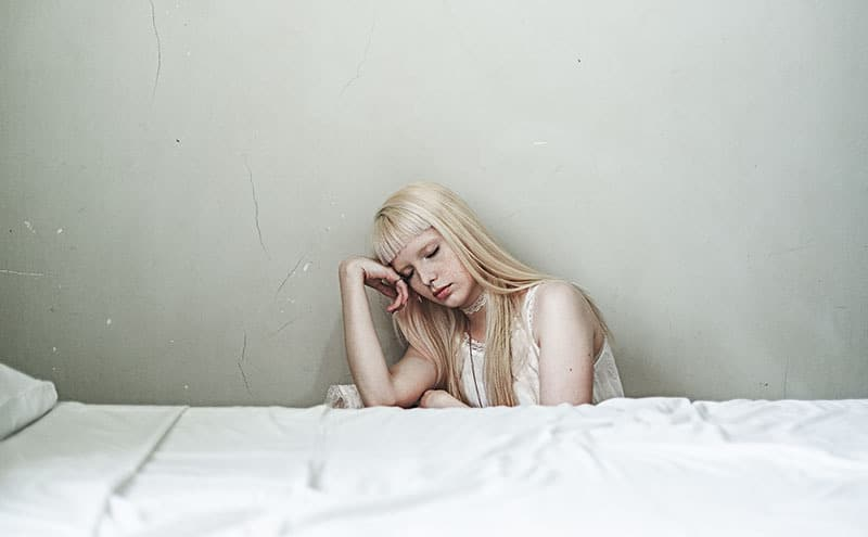 Blond woman sitting next to her bed with closed eyes.