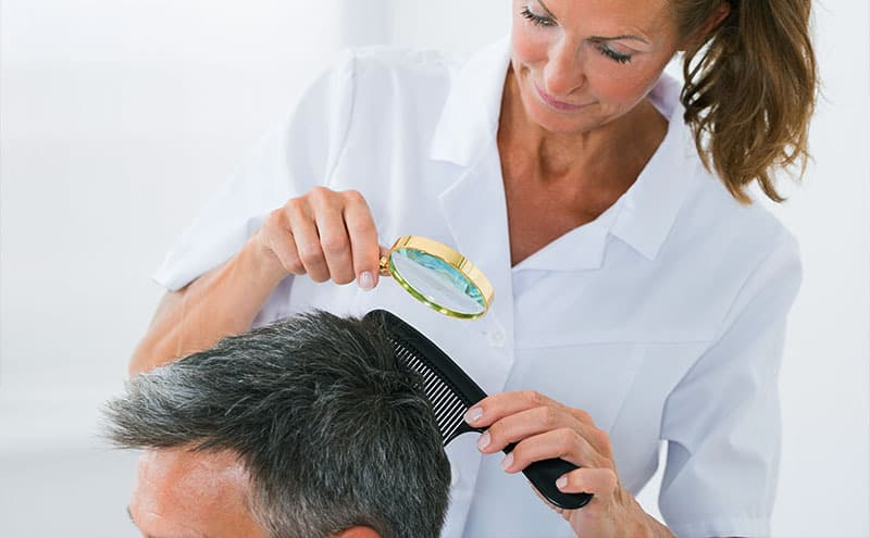 Professional inspecting man's hair with magnifier and hairbrush to tell lice vs dandruff.