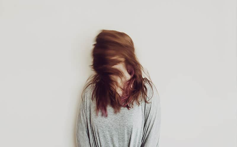 Woman standing in front of light grey background, shaking her hair in a way that it hides her face.