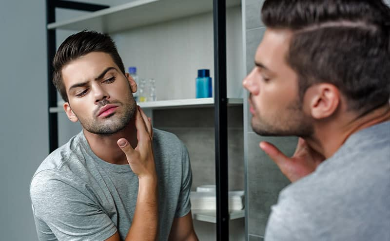 Young man observing grey hair in his beard at the mirror.