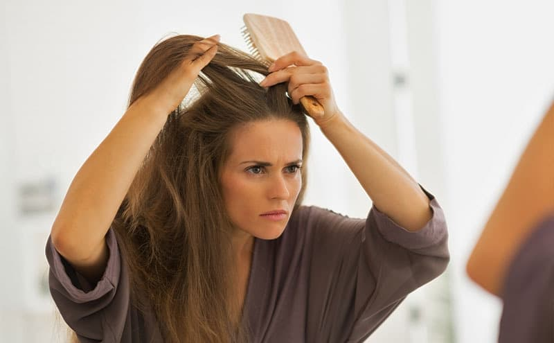 Woman observing her hair, wondering about premature grey hair causes.
