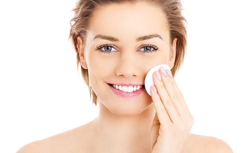 Close up of beautiful young woman with shortish light brown hair and blue eyes cleaning her face with a white pad while smiling.
