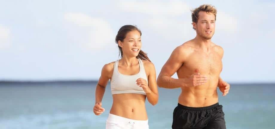fit people running along a beach.