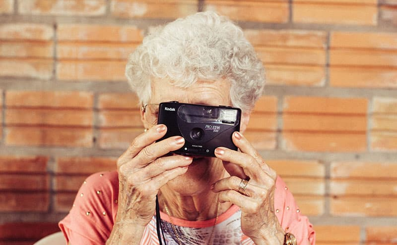 Sweet old lady with a Kodak camera taking a picture of you.