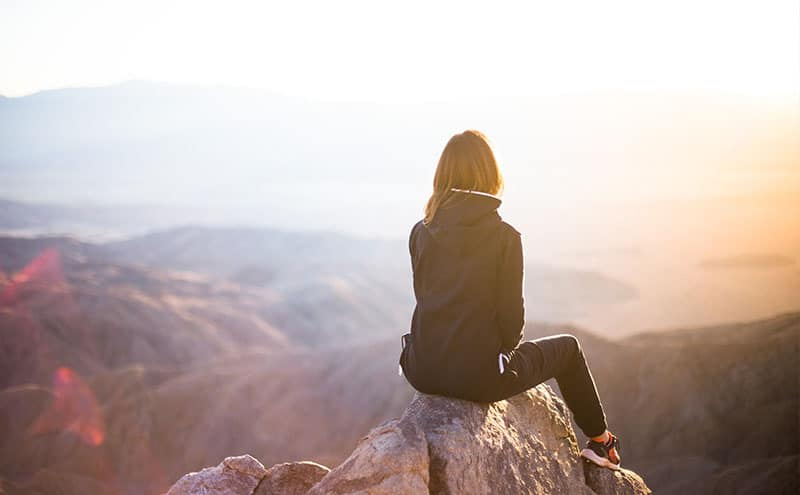 Woman sitting on mountain, looking at the peaceful scenery.