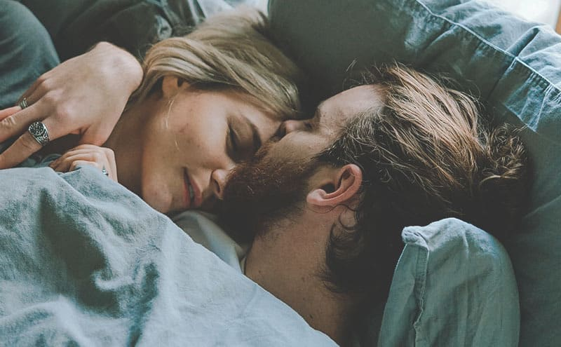 A woman and a man sleeping in a bed