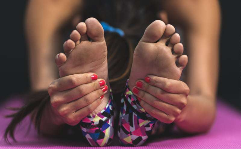 Woman stretching with her hands on the bottom of her feet