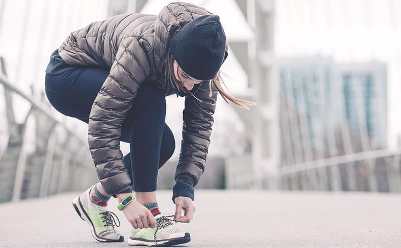 a female runner stopping to tie the Best Running Shoes for Overpronation while running on a bridge in the cold.