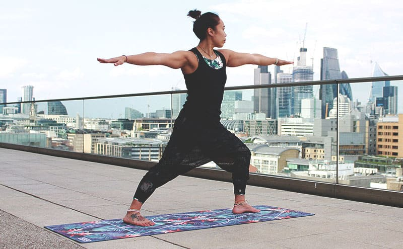 A person practicing yoga on top of a building using a yoga mat for travel.