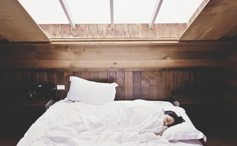 A woman asleep and tucked in and comfortable thanks to the best bed risers for queen bed.