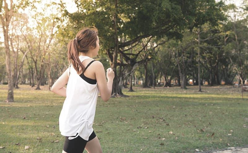 A woman in a white shirt jogging in a park and following her progress with the best fitness tracker for women.