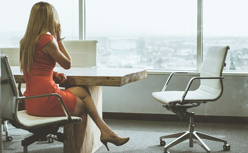 Business woman in comfortable high heels in an office at a desk sitting with the best high heel inserts in her shoes.