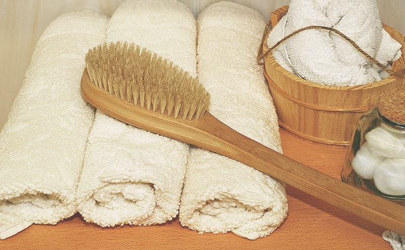 The best dry brush placed on a stack of towels in a bathroom.
