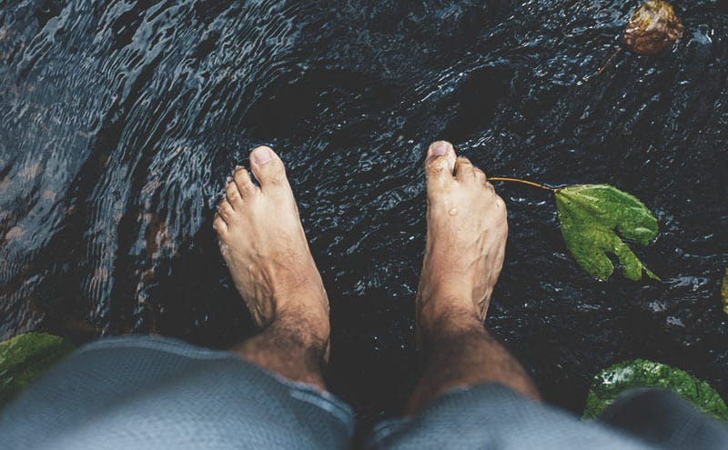 Feet of a man resting in river water with toes stretched nicely by best toe stretchers for pain-free feet.