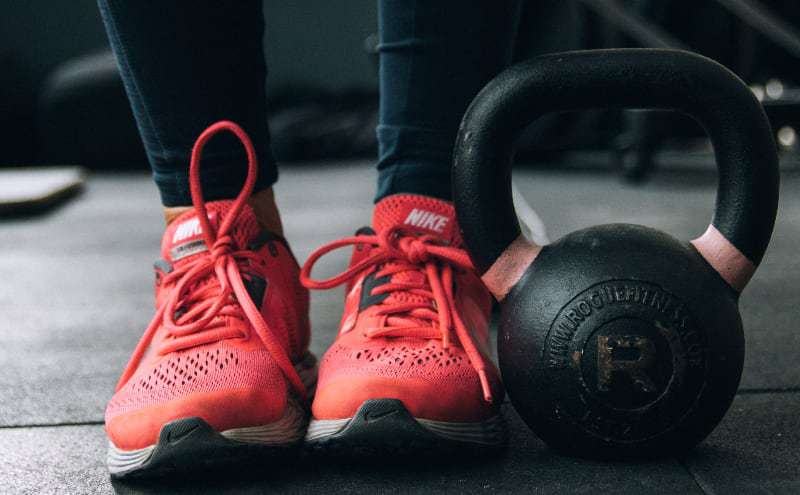 legs of a fitness woman with a kettlebell