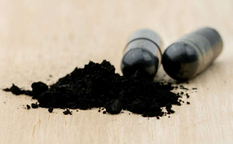 Powders of activated charcoal on brown wooden table and blur capsule background.