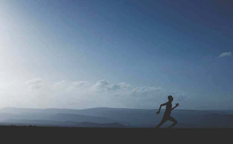 Silhouette of a runner using the best toe separators for runners with a beautiful landscape in the background.