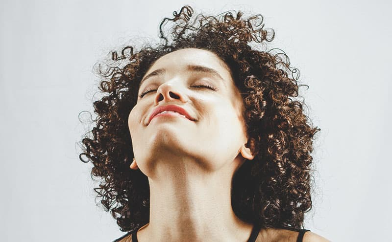 Smiling woman with curly hair enjoying the benefits of the best shampoo for permed and colored hair.