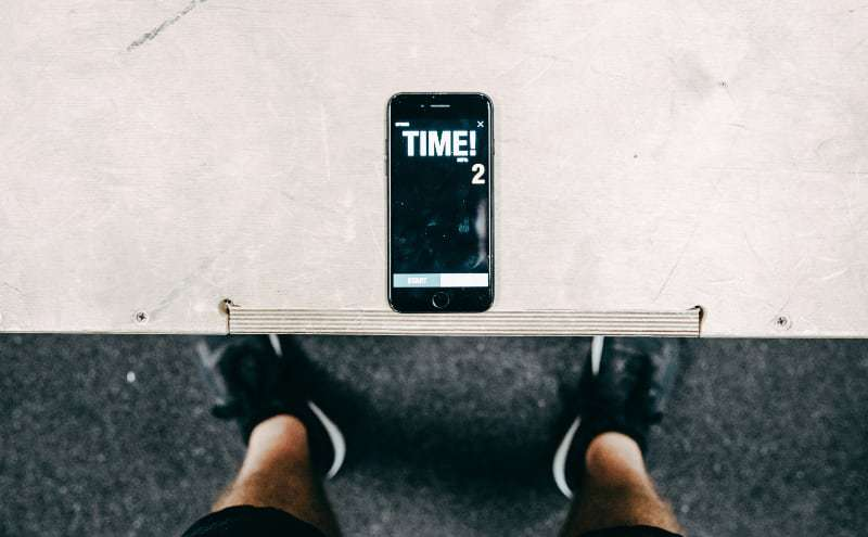 Sportsman using smartphone with time tracker in gym.