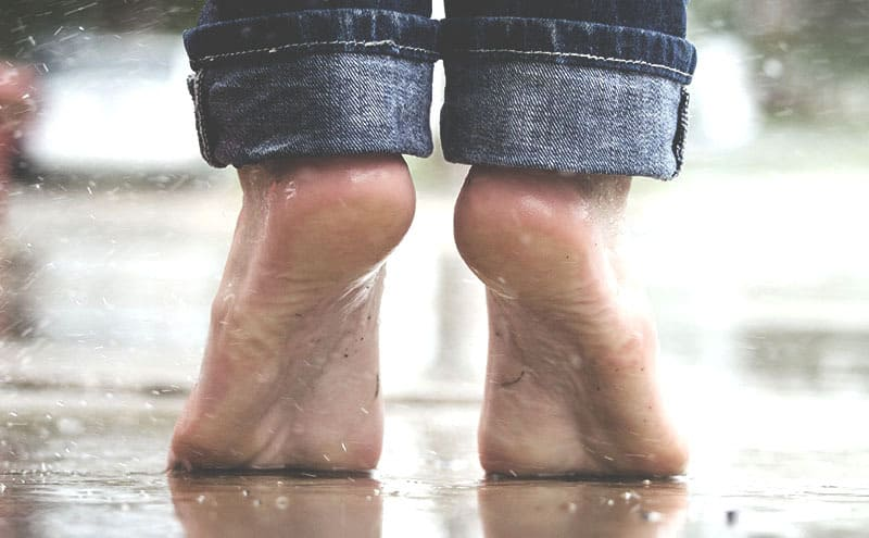 Barefoot person stretching without their shoes that have the best insoles for heel pain.