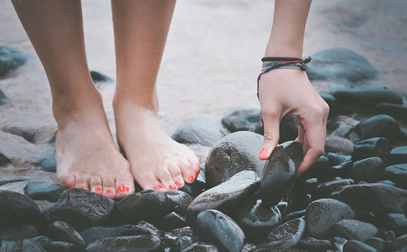 A barefoot woman considering using a large pebble instead of the best foot massage balls to massage her feet.