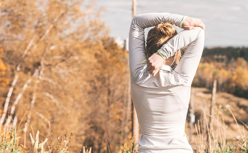 A fit woman stretching during her run in the countryside after healing her shoulders with the best shoulder brace.