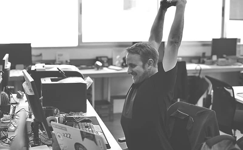 A man gleefully stretching in an office at his desk after he finished a quick exercise with one of the best pedal exercisers.