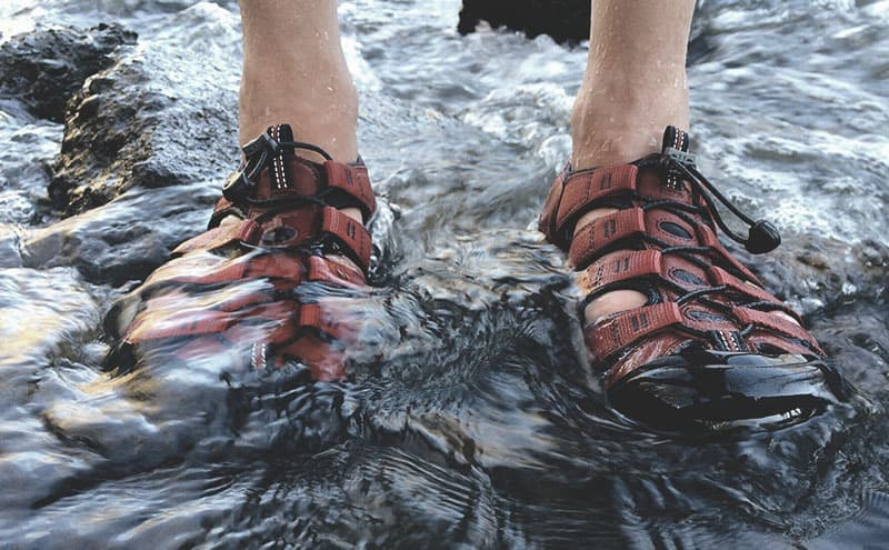 A person with the best walking sandals standing in water.
